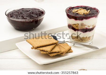 Healthy dessert with natural yogurt, full grain biscuits and black currant jam. - stock photo