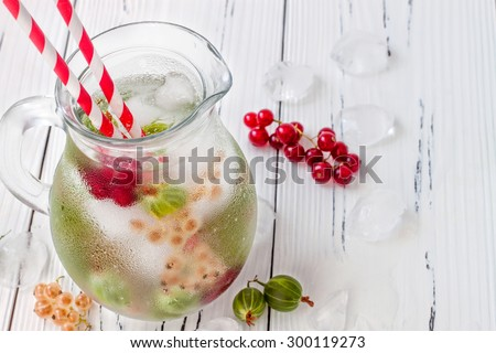 Healthy detox berry infused flavored water. Summer refreshing homemade drink with gooseberries and white and red currant on white wooden table - stock photo