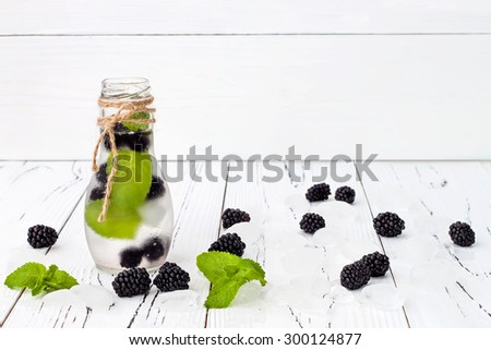 Healthy detox water with blackberry and mint. Cold refreshing berry drink with ice on white wooden table. Copy space background - stock photo