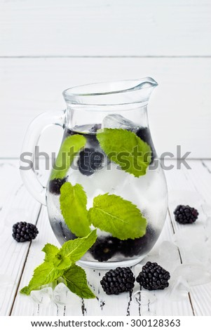 Healthy detox water with blackberry and mint. Cold refreshing berry drink with ice on white wooden table - stock photo