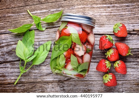 Healthy detox water with strawberries and basil - stock photo