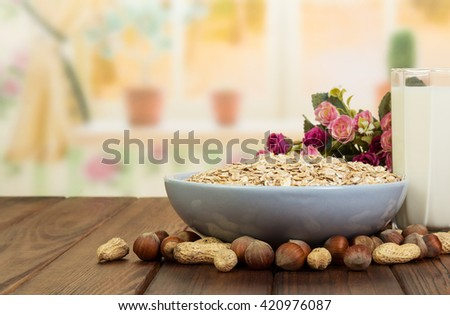 Healthy diet for adults: a bowl of oatmeal, a glass of milk and nuts on the background of the kitchen. - stock photo
