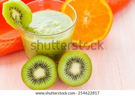 Healthy diet: fruit juice, kiwi and orange on wooden table - stock photo