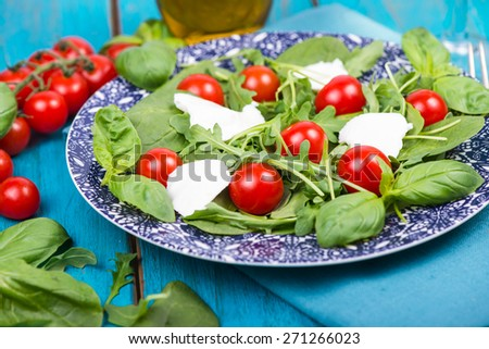 Healthy diet salad with tomatoes and mozzarella served on plate - stock photo