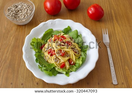 healthy dinner consists of salad and pasta with tomatoes and sunflower seeds - stock photo