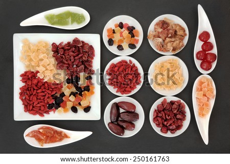 Healthy dried fruit selection in white porcelain bowls over slate background. - stock photo