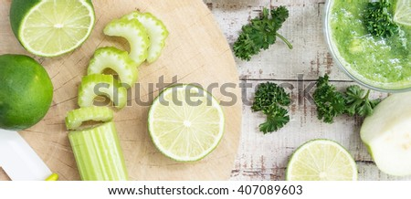 Healthy drink ingredients on white wooden table. Celery stalk, lime, green apple, guava with knife on cutting board. All in focus. Vegan, diet, vegetarian food, detox. - stock photo