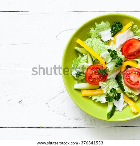 Healthy eating and Diet concept. Green Plate with fresh vegetables salad on white wooden table. - stock photo
