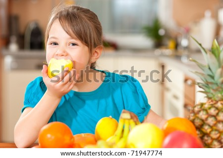 Healthy eating - child eating an apple, lots of fresh fruit on the table in front - stock photo