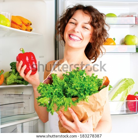 Healthy Eating Concept. Diet. Beautiful Young Woman near the Fridge  with healthy food. Fruits and Vegetables in the Refrigerator. Vegan food - stock photo