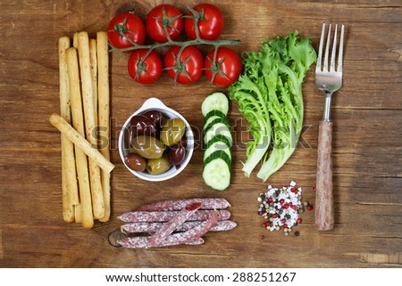 Healthy eating concept food set - sausages, bread sticks, tomatoes, cucumbers, lettuce, olives, top view - stock photo