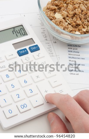 Healthy eating concept - man calculate his daily nutrition intake. Muesli in glass bowl, calculator, calendar and nutrition chart. - stock photo