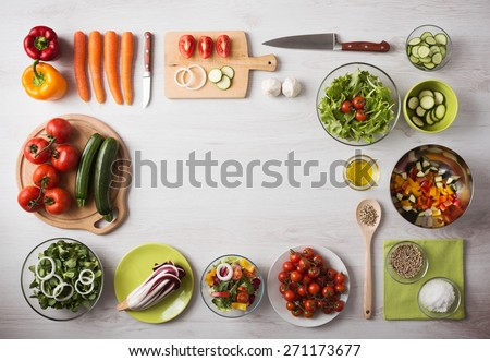 Healthy eating concept with fresh vegetables and salad bowls on kitchen wooden worktop, copy space at center, top view - stock photo