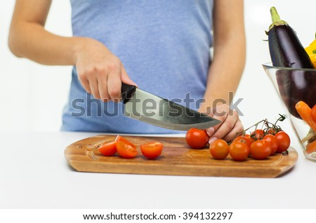 healthy eating, cooking, vegetarian food, dieting and people concept - close up of woman chopping tomatoes with knife on cutting board - stock photo