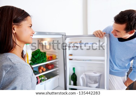 healthy eating couple get fresh vegetables out of the fridge to cook food - stock photo