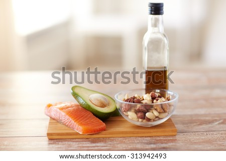 healthy eating, diet and culinary concept - close up of salmon fillets, avocado, olive oil bottle and nuts in glass bowl on table - stock photo