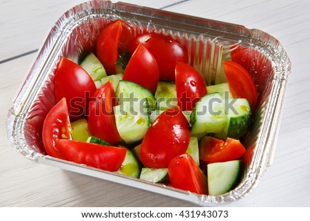 Healthy eating, diet concept. Healthy lunch, Take away organic food. Weight loss diet, food take away in aluminium box. Healthy food. Vegetable salad from tomatoes and cucumbers at white wood, closeup - stock photo