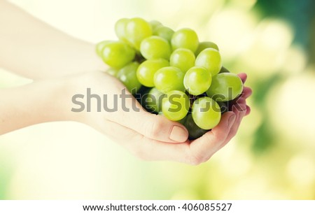 healthy eating, diet, organic food and people concept - close up of woman hands holding green grape bunch over natural background - stock photo
