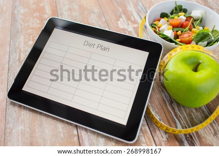 healthy eating, dieting and weigh loss concept - close up of diet plan on tablet pc screen, green apple, measuring tape and sald - stock photo