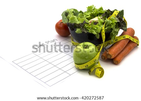 healthy eating, dieting, slimming and weigh loss concept - close up of diet plan paper green apple, tomato, carrot, measuring tape and salad - stock photo