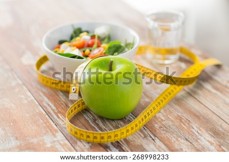 healthy eating, dieting, slimming and weigh loss concept - close up of green apple, measuring tape and salad - stock photo