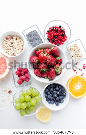 healthy eating, dieting, vegetarian food and people concept - close up of fruits and berries in bowl on table - stock photo