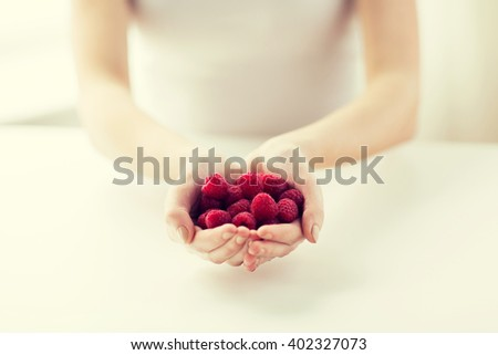 healthy eating, dieting, vegetarian food and people concept - close up of woman hands holding raspberries at home - stock photo