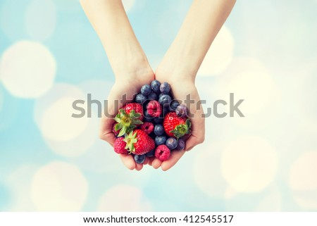 healthy eating, dieting, vegetarian food and people concept - close up of woman hands holding different ripe summer berries over blue lights background - stock photo