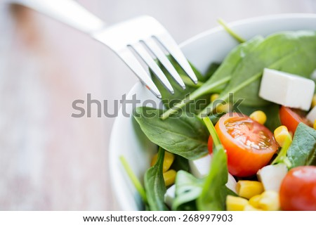 healthy eating, dieting, vegetarian kitchen and cooking concept - close up of vegetable salad bowl and fork at home - stock photo