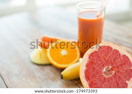 healthy eating, food and diet concept - close up of fresh juice glass and fruits on table - stock photo