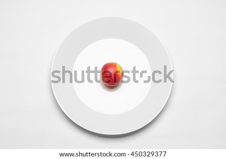 Healthy eating in the restaurant and diet Topic: beautiful ripe nectarine on a white plate lies on an isolated white table in studio top view - stock photo