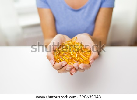 healthy eating, medicine, health care, food supplements and people concept - close up of woman hands holding pills or fish oil capsules at home - stock photo