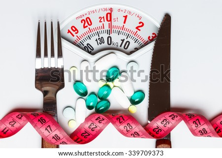 Healthy eating, medicine, health care, food supplements and weight loss concept. Pills with measuring tape on white scales - stock photo
