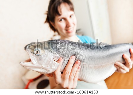 Healthy eating seafood - beauty young smiling woman hand holding raw salmon or trout fish food at kitchen - stock photo