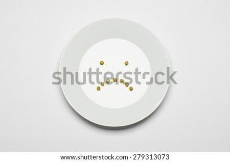 Healthy eating topic: green peas lying on a white plate on a white table in the studio, a sad smile top view - stock photo