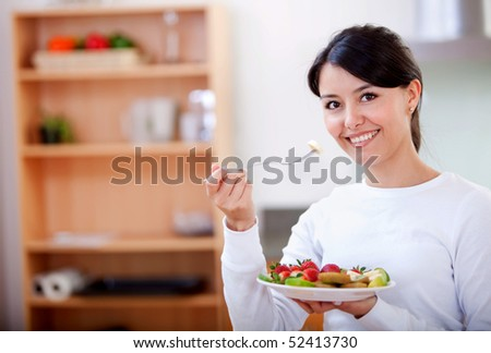 Healthy eating woman with fruit salad smiling - stock photo