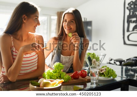 Healthy Eating Women Cooking Salad. Beautiful Smiling Vegan Girls Going To Eat Fresh Green Organic Vegetables In Kitchen. Happy People Enjoying Fitness Food. Detox Diet, Weight Loss Nutrition Concept - stock photo