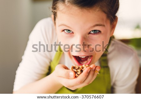 Healthy eating, young girl eating walnuts - funny portrait - stock photo