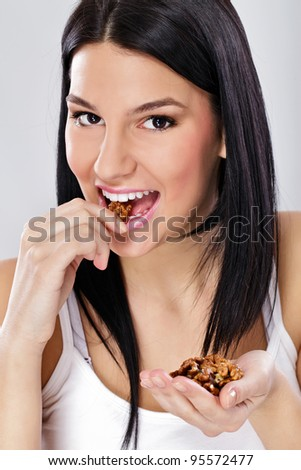 Healthy eating, young woman eating shelled nuts - stock photo
