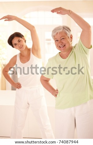 Healthy elderly woman doing exercises with personal trainer at home, smiling. - stock photo