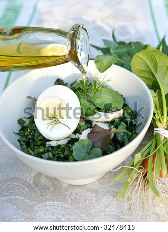 Healthy enrich salad with spring native-grasses weed and vegetable plants, arranged with boiled eggs in a white bowl on table-cloth decorated with a bunch of weed herbs - stock photo