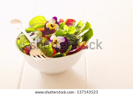 Healthy farm fresh herb salad with leafy greens and nasturtium flowers served in a white bowl with a fork on a wooden white table - stock photo