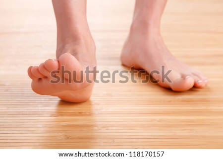 Healthy female feet on wooden floor - stock photo