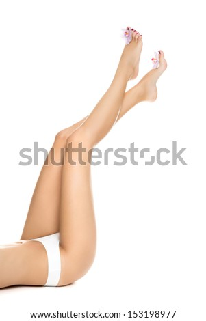 Healthy female   Legs. Spa. Long woman legs and orchids isolated on white background. Skin care. Depilation. Epilation - stock photo