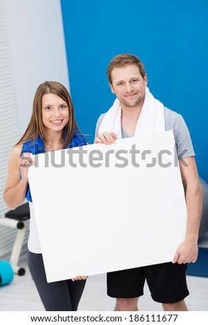 Healthy fit young couple standing in a gym in their sportswear holding a blank white sign with copyspace for your text or advertisement - stock photo