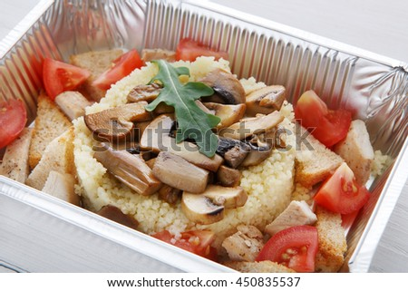 Healthy food and diet concept. Take away of fitness meal. Weight loss nutrition in foil boxes. Couscous with mushrooms closeup at white wood - stock photo