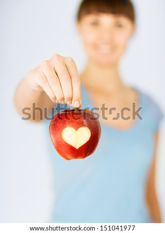 healthy food and lifestyle - woman hand holding red apple with heart shape - stock photo