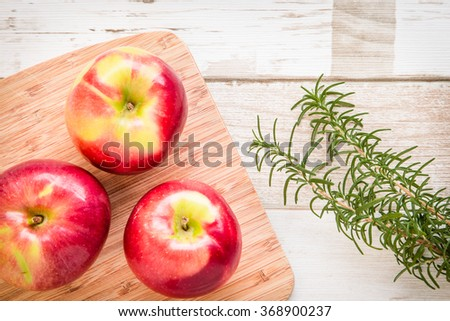 Healthy food arrangement with three red apples on a wooden board and rosemary leaves on a rustic wooden table. View from above/top. - stock photo