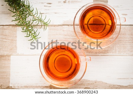 Healthy food arrangement with two glass cups of herbal or black tea and rosemary leaves on a rustic wooden table. View from above/top. - stock photo