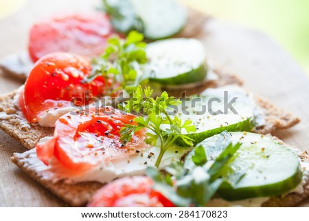 Healthy food, bright sandwiches. Finnish rye crisp bread, soft cheese, cucumber, tomato, parsley and black pepper - stock photo